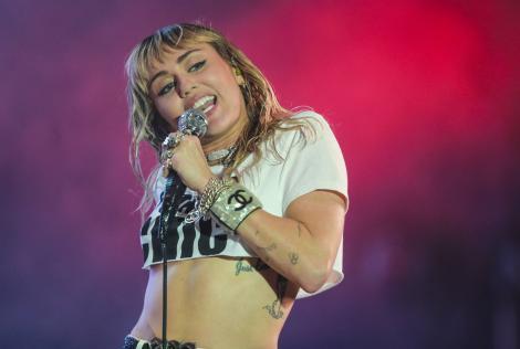 Miley Cyrus, pe scenă, într-un tricou alb, cu abdomenul la vedere
