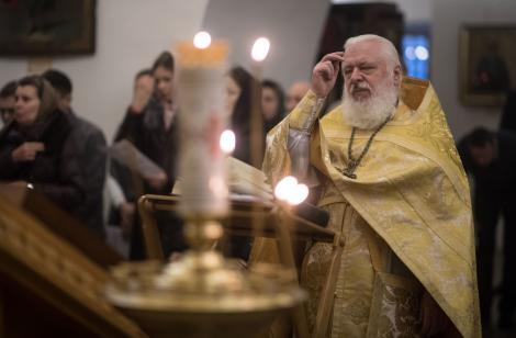 Preot, fotografiat in timpul slujbei de pe 6 decembrie, cand se sarbatoreste Sfantul Nicolae