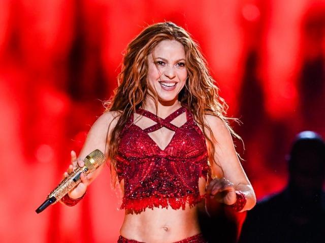 Shakira pe scena, poarta un top si o fusta de culoarea rosu, tine microfonul in mana si zambeste