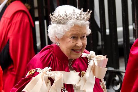 Regina Angliei poartă pe cap o coroană mare, strălucitoare