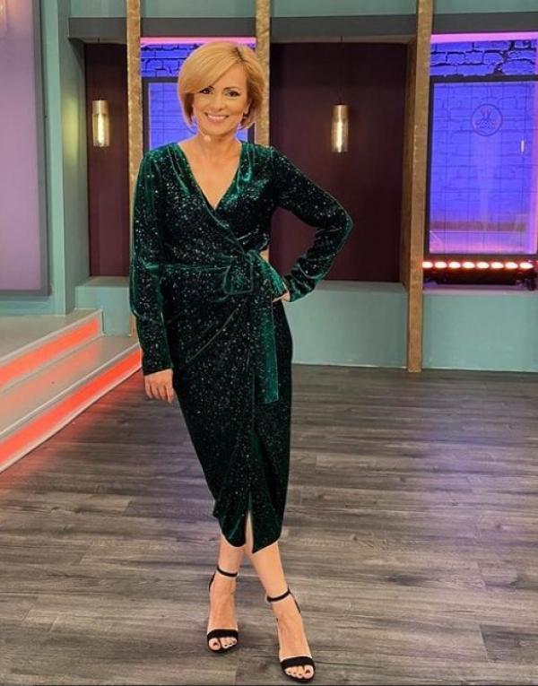 Simona Gherghe pe platou, imbracata intr-o rochie de culoarea smaraldului, sclipitoare.
