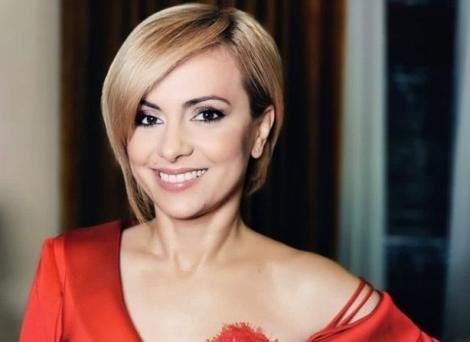 Simona Gherghe cu noul look, o tunsoare bob-scurt, imbracata intr-o bluza rosie.