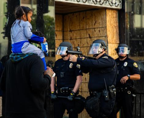 """""""Nu e trucaj, nu e nimic modificat! Asta se întâmplă pe străzi!"""" - Polițist, cu arma scoasă și degetul pe trăgaci, în fața unei copile. Protestele din SUA continuă"""
