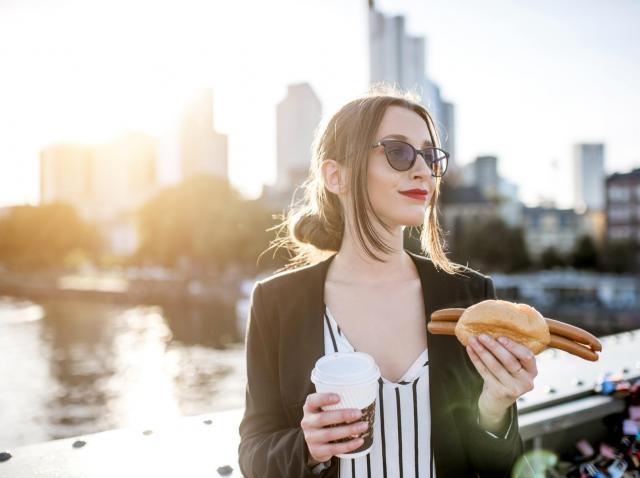 femeie care mananca un hot dog in aer liber