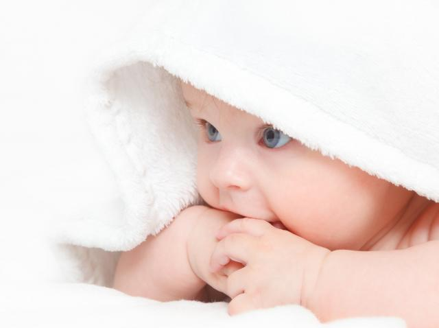 bebelus intins pe burtica si cu un prosop pe cap