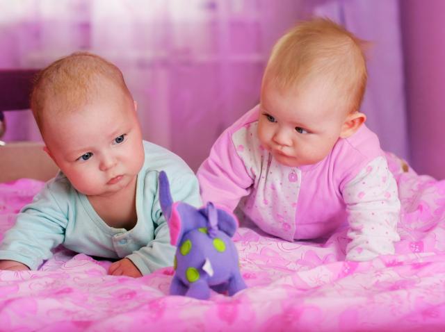 bebelusi imbracati in haine albastre si roz