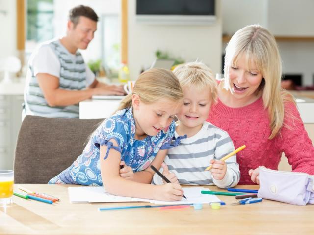 mama cu doi copii colorand la masa