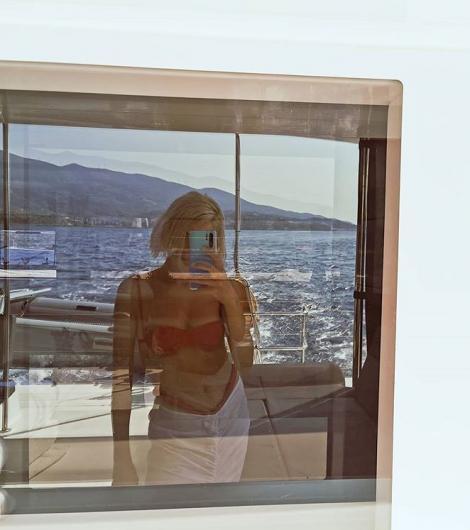 lidia buble in costum de baie isi face selfie in reflexia unei ferestre