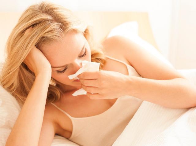 femeie racita care sta in pat si isi  sufla nasul