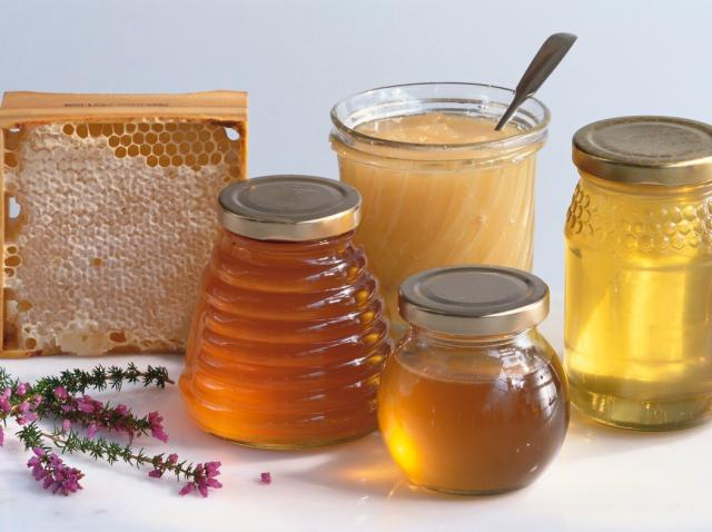 miere in borcane, langa un fagure de miere, pe o masa alba