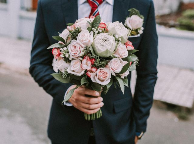 barbat la costum tinand un buchet de flori in mana