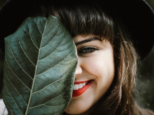 fata cu palarie neagra si frunza verde in dreptul fetei, zambind