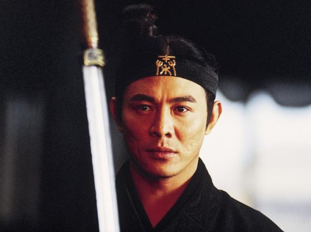 Jet Li, într-o scenă din filmul ''Hero'' (2002), privește atent către o sabie, având pe cap o banderolă și părul prins în coc