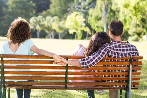 un cuplu, femeie si barbat pe banca, iar barbatul se tine de mana cu o alta femeie, la capatul bancii