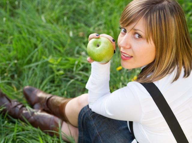 o fata cu bluza alba stand pe iarba cu un mar verde in mana