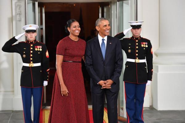 Michelle și Barack Obama, stau în fața unei clădiri și le zâmbesc fotografilor aflați în fața lor