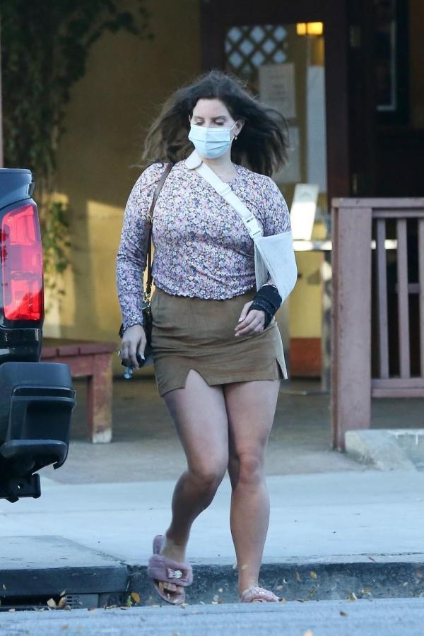 Lana Del Rey, cu mâna în ghips, mască de protecție, fustă mini și o bluză înflorată