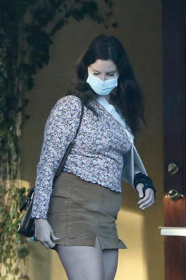 Lana Del Rey, cu mâna în ghips, mască de protecție, fustă mini și o bluză înflorată, în parcarea unui restaurant