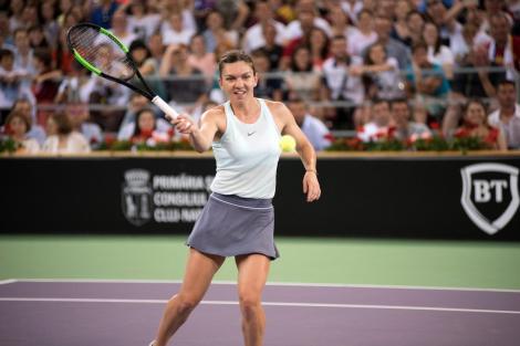 Simona Halep, într-un maiou alb, pe terenul de tenis
