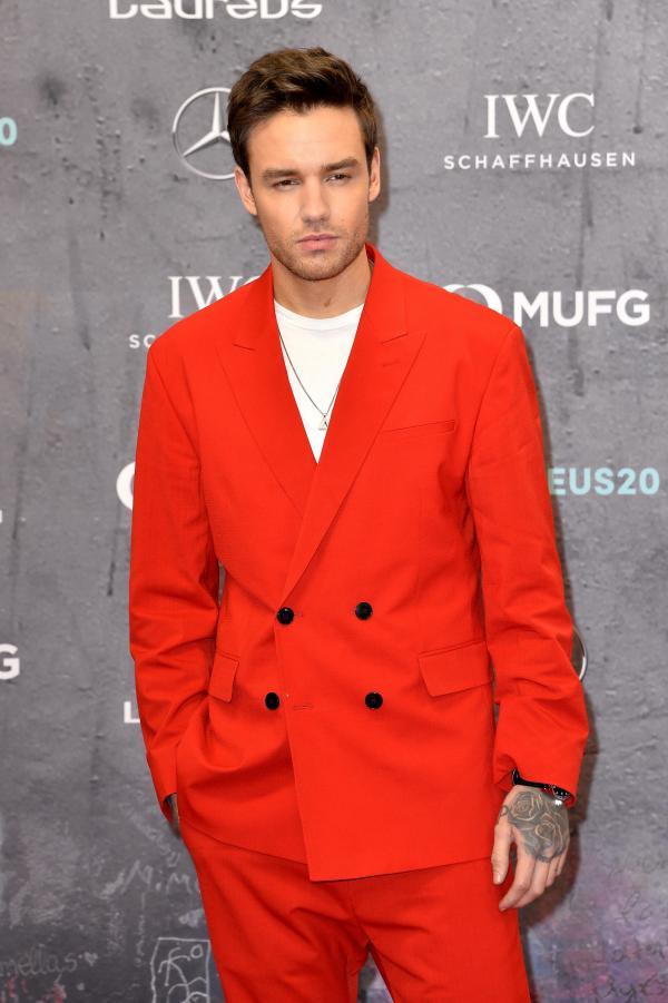 Liam Payne, privește direct în obiectivul aparatului de fotografiat și este îmbrăcat cu un sacou roșu, cu două rânduri de nasturi