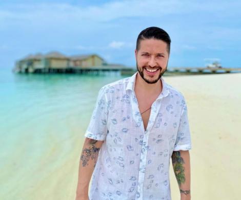 Jorge la plaja in Maldive, intr-o camas alba cu floricele albastre