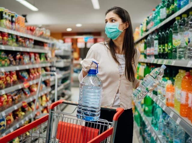 Tânără în supermarket, purtând mască, cumpărând sticle cu apă
