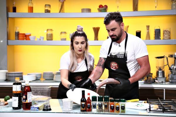 Adda și Cătălin Rizea, gătind la Chefi la cuțite, purtând șorțuri negre, cu sigla emisiunii