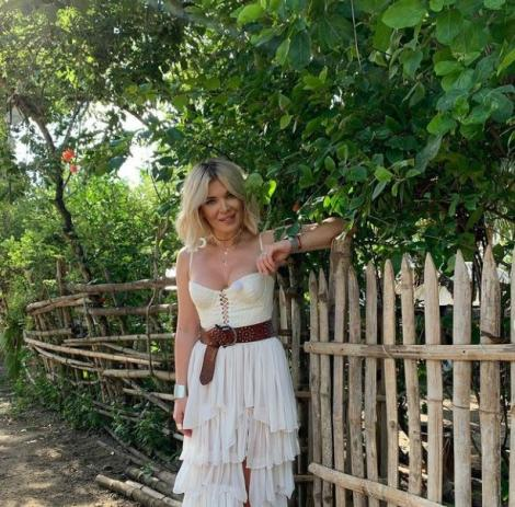 Gine Pistol intr-o rochie alba, se sprijina de un gard din el, iar in spatele ei este foarte multa vegetatie