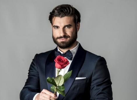 Andi Constantin, burlacul sezonului 6 al show-ului, îmbrăcat la costum, cu papion, ține în mână un trandafir roșu și zâmbește mistrios