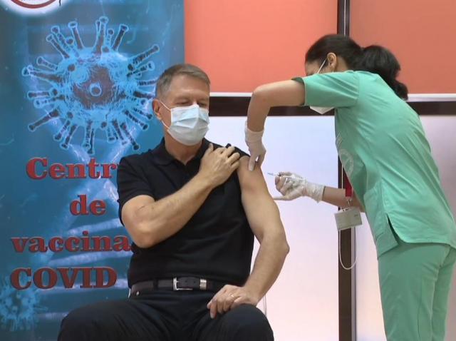 Klaus Iohannis, într-un tricou negru, în timpul vaccinului