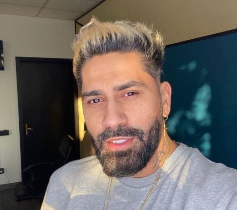 Connect-R, cu părul blond și îmbrăcat într-un tricou gri