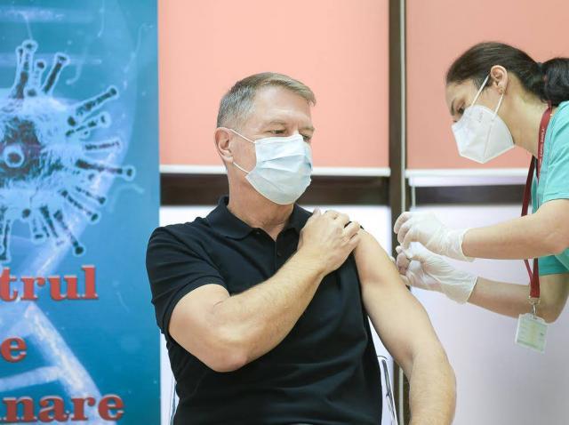 Klaus Iohannis, într-un tricou negru, încordându-și mușchii, în timpul vaccinului