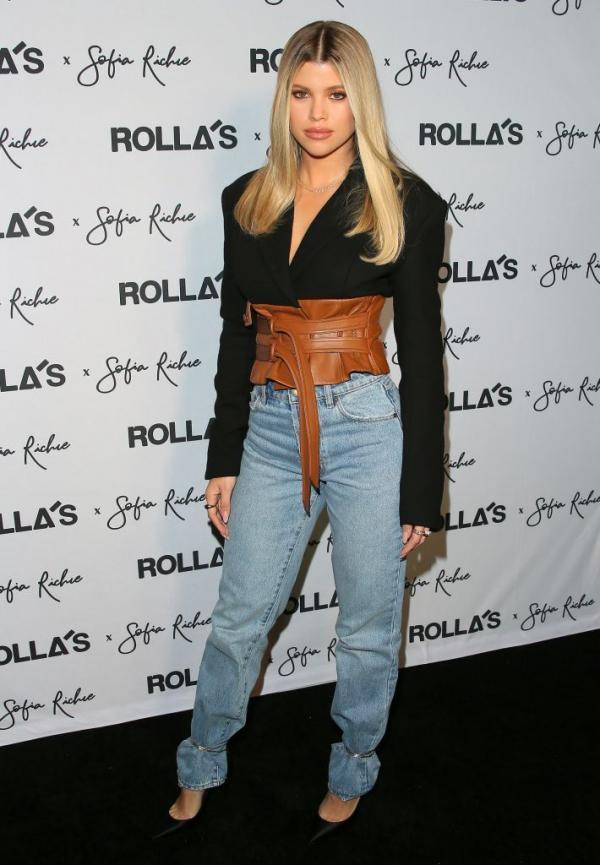 Sofia Richie cu parul blond si drept, imbracata intr-o bluza neagra si pantaloni albastri