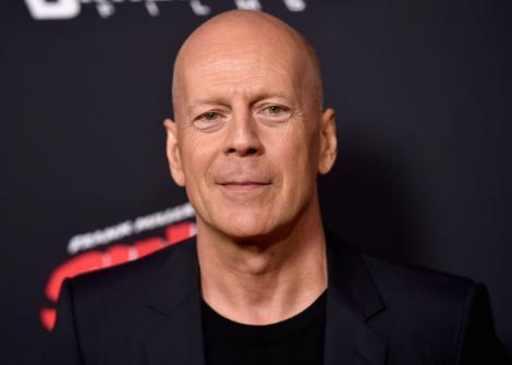 Bruce Willis pe covorul rosu intr-un costum negru