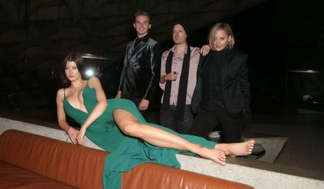 sarah mcdaniel intinsa pe o canapea in timp ce e imbracata intr-o rochie verde