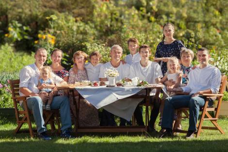 Familie numeroasa la o masa de picnic, pe iarba