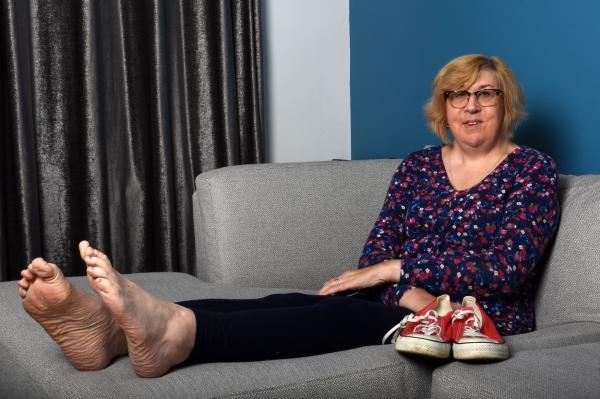 julie felton intinsa pe o canapea, in timp ce are picioarele goale