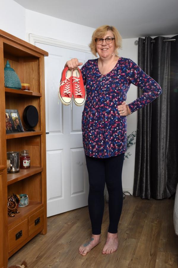 julie felton in picioare, cu o pereche de tenisi de culoare rosie in mana dreapta
