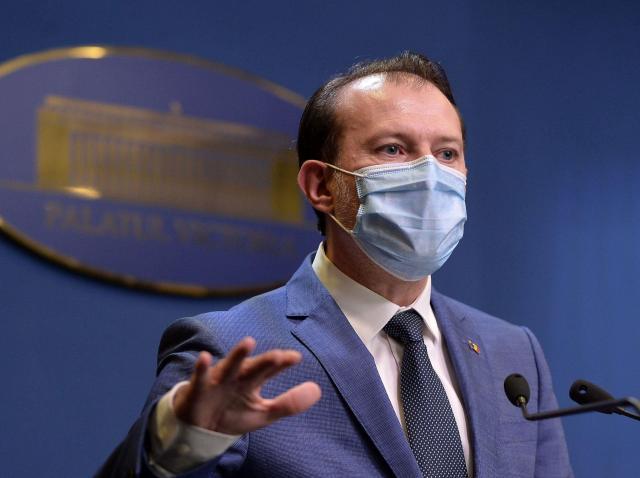 Florin Cîțu imbracat intr-un costum albastru și cu cravata alabstra, poarta masca