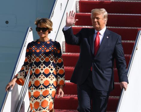 Donald Trump, purtând costum și cravată și Melania Trump într-o rochie cu negru și portocaliu, coborând din avion, în Flordia