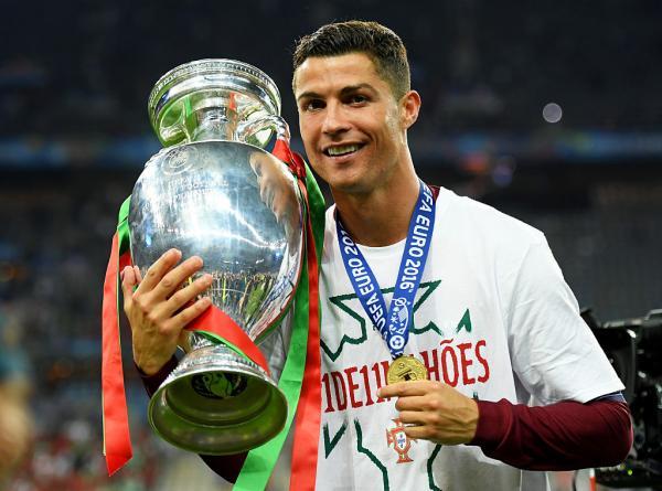 Cristiano Ronaldo cu un trofeu în mână și o medalie la gât