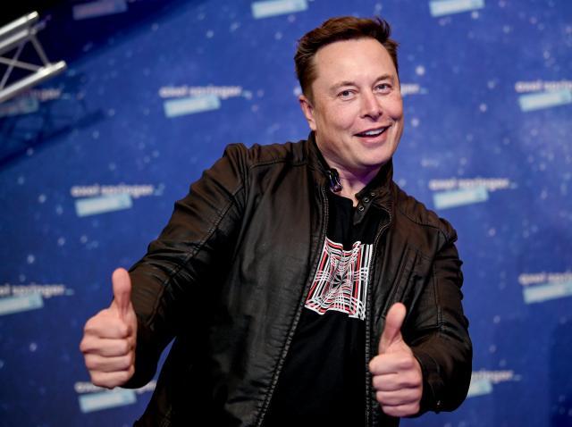 Elon Musk, covor rosu, geaca neagra si tricou negru cu logo