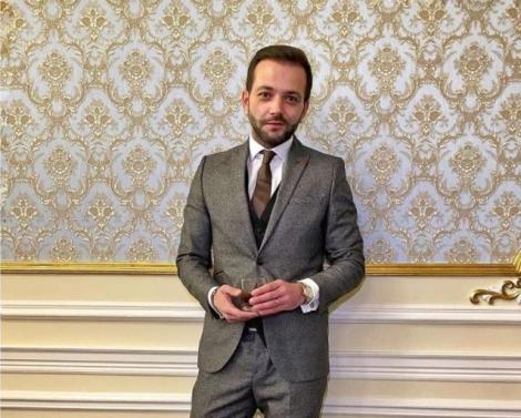 Mihai Morar intr-un costum gri, cravată vișinie și cămașă albă, are și un pahar în mână