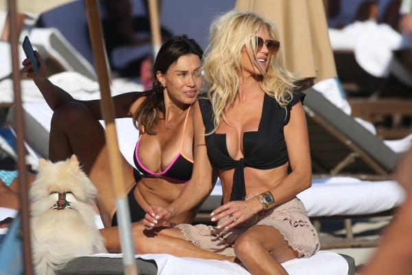Victoria Silvstedt la plajă, bluza neagra, fusta crem, sezlong