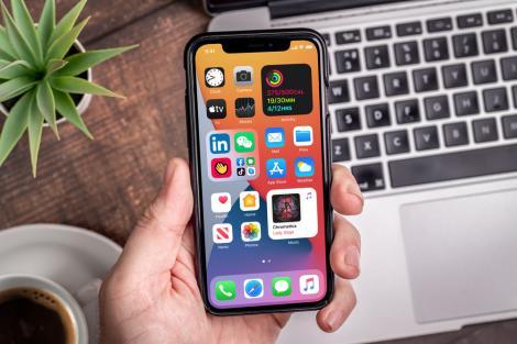 Iphone 12 tinut in mana, langa un laptop, o planta si o cafea
