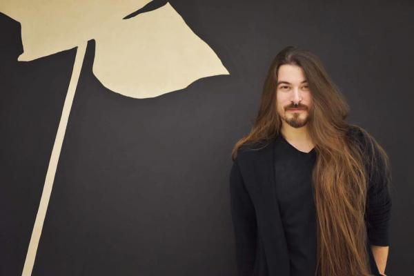 Massimo Volpe, cu părul despletit, făcând o poză cu spatele la un perete cu element decorativ
