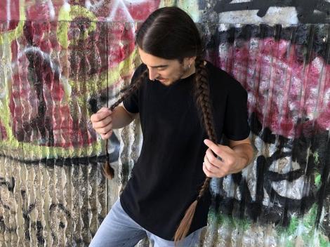 Massimo Volpe, cu părul împeltit, făcând o poză în oraș