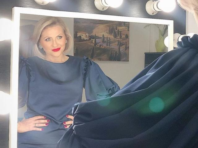 mirela vaida fotografiata cu spatele spre camera de filmat, cu imaginea ei care se reflecta in oglinda