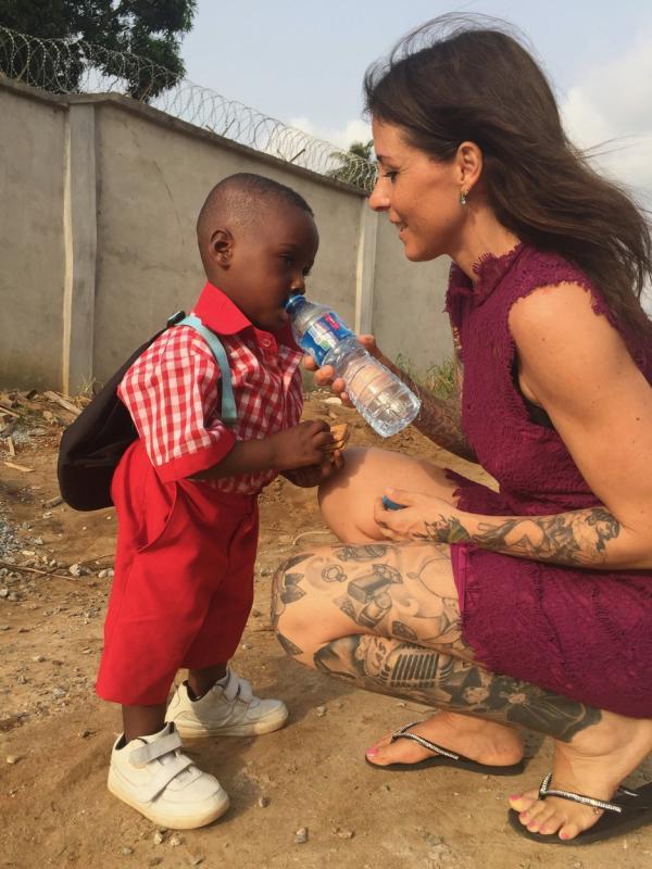 Hope, băiețelul din Nigeria abandonat să moară de foame, cu uniformă de școlar, primind apă de la Anja Loven