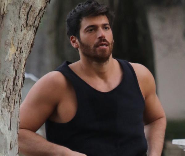 Actorul Can Yaman, purtând un maieu negru, în timp ce face jogging